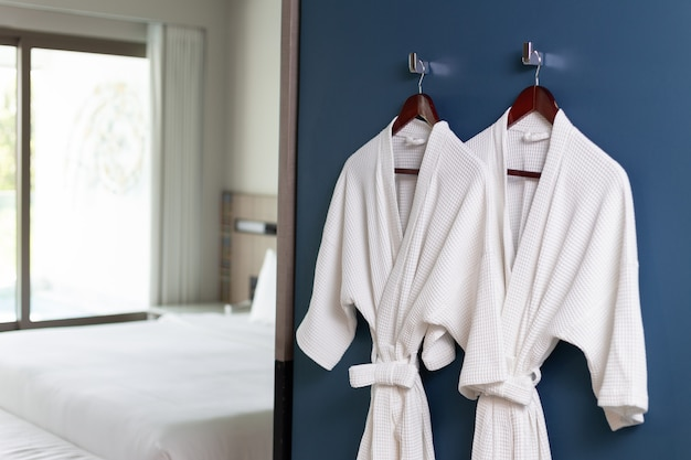 White bathrobes hanging on wall
