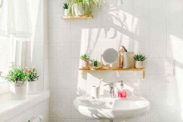 화창한 날 창 옆에 세면대가 있는 친환경적인 스타일의 흰색 욕실. 나무 대나무 선반과 배경에 그림자에 녹색 계획. 제로 웨이스트와 지속 가능한 라이프 스타일. 웰빙
