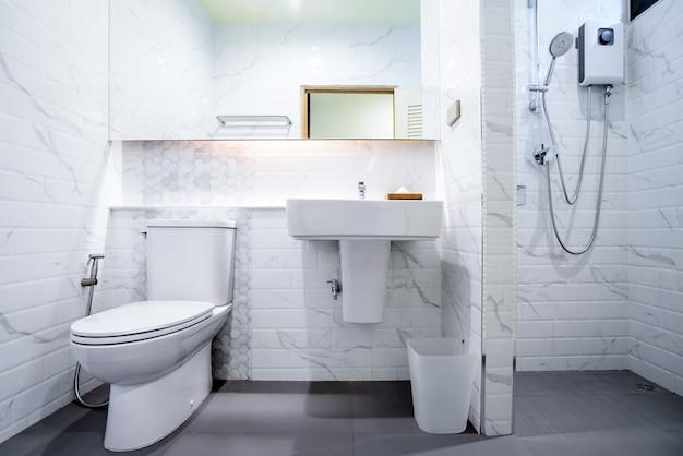 シャワー、トイレ、洗面台付きの白いバスルームのインテリア