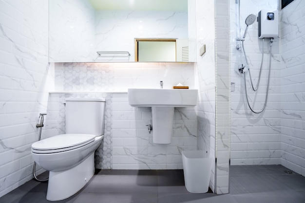 White bathroom interior with a shower, a toilet and a sink