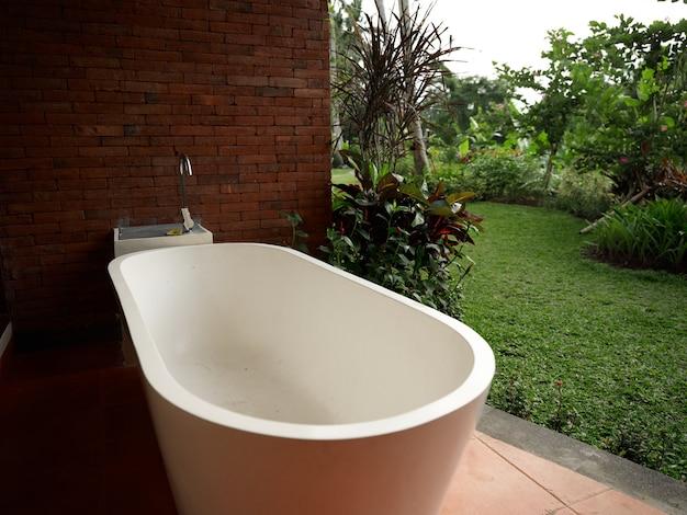 ポーチ ルーム デザインの白いバスルームと自然の風景を背景に