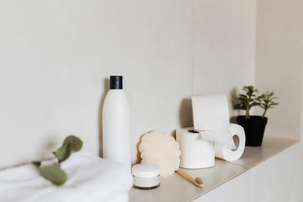 욕실 액세서리가있는 흰색 욕실. 호텔 청소 개념. 가정용 개념. 수건, 샴푸, 크림, 화장지, 식물, 칫솔.