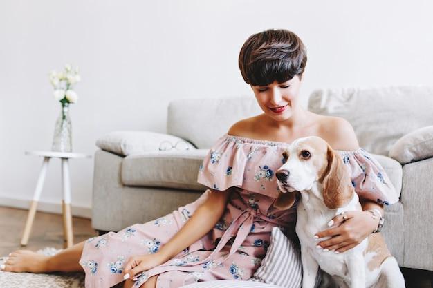 Cane beagle bianco con orecchie marroni che guarda lontano mentre sorridente ragazza bruna seduta accanto
