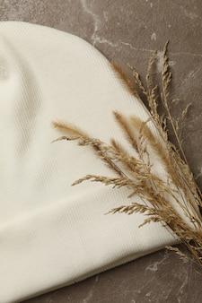 Белая шапочка и полевые растения на серой поверхности