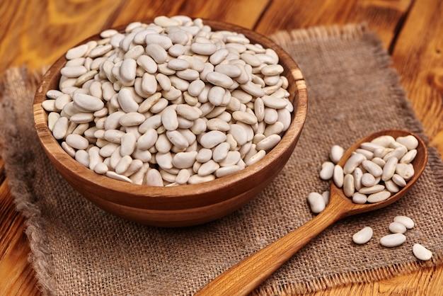 흰 콩 흰 콩, 소박한 배경의 전체 나무 숟가락과 나무 그릇. 확대.