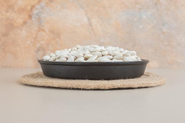 Fagioli bianchi in vassoi per alimenti su cemento.