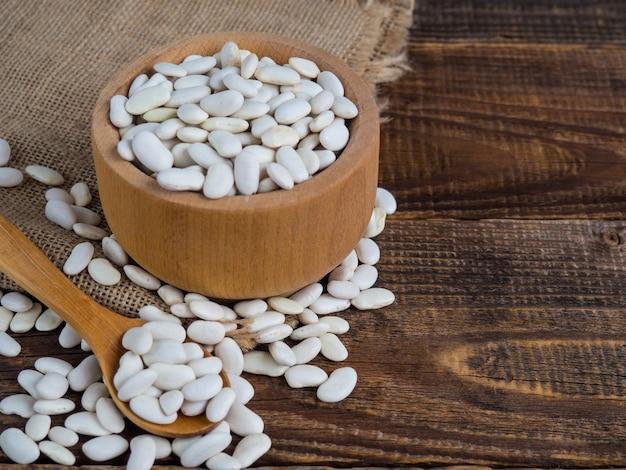 古い木製のテーブル、マメ科植物、コピースペースの木製ボウルに白インゲン豆