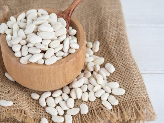 Белая фасоль в деревянной ложке на белом деревянном столе, копией пространства
