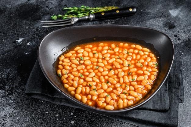 皿にトマトソースをかけた白豆。黒の背景。上面図。