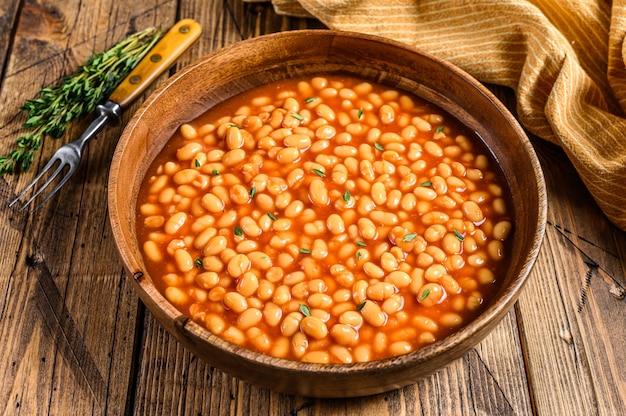 木の板にトマトソースをかけた白豆。木製の背景。上面図。