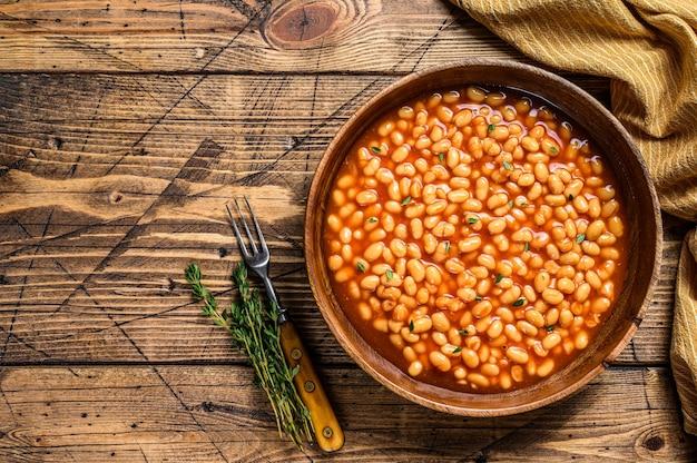 木の板にトマトソースをかけた白インゲン豆。木製のテーブル。上面図。