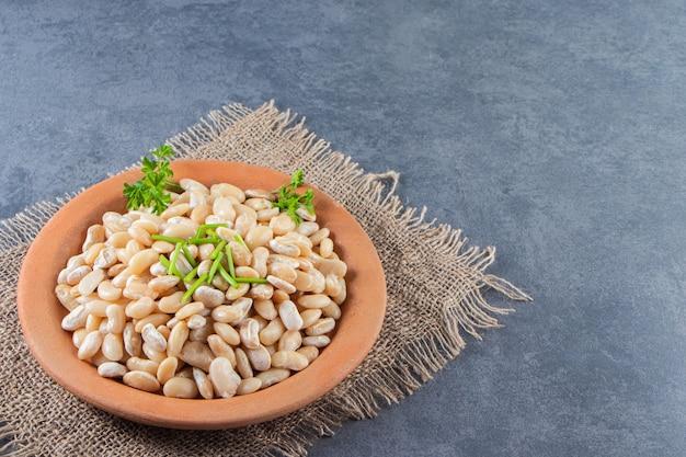 大理石の背景に、黄麻布ナプキンのプレートに白インゲン豆。