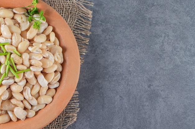 大理石の表面の黄麻布ナプキンの皿の上の白豆