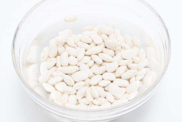 ガラスのボウルに水に浸した白豆を白い背景にクローズアップ