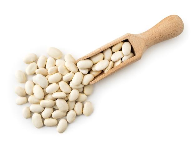 白い背景の上に木のスプーンからこぼれた白豆