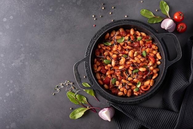 검은 냄비에 양파와 허브와 함께 토마토 소스에 끓인 흰 콩, 평면도