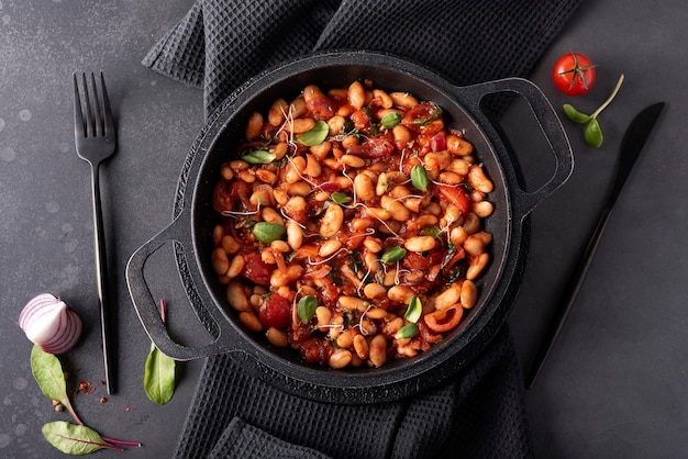 White beans stewed in tomato sauce with onions and herbs in a black pan, top view