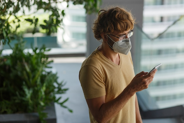 White bearded adult man using smartphone while wearing surgical mask on an industrial wall. health, epidemics, social media.