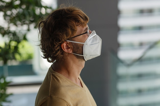 産業の壁にサージカルマスクを身に着けている白いひげを生やした成人男性。健康、伝染病、ソーシャルメディア。