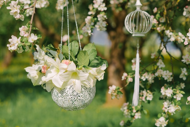 White beautiful flowers in a silver round vase hang on a blooming apple tree. wedding decor