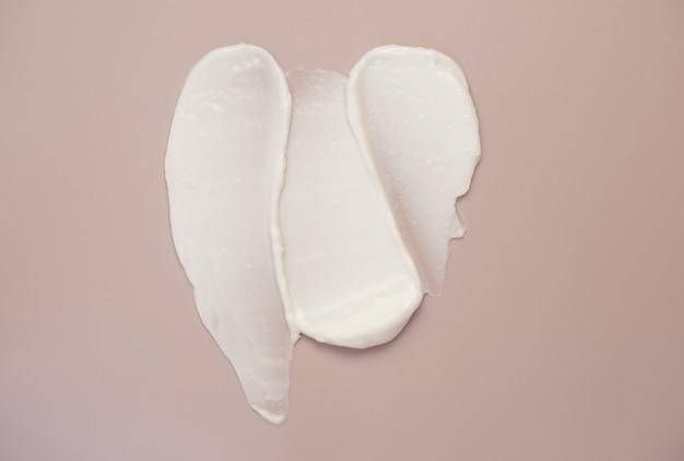 Белый косметический крем-лосьон с хайлайтером мазок образца пятна на розовом фоне