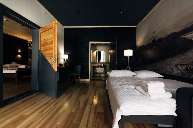 美しいホテルの木造の部屋の白いベッド