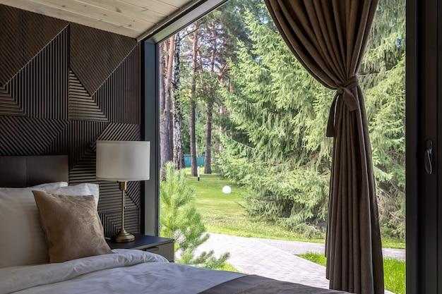 나무 침실에 흰색 침대, 이불, 베개가 있습니다. 호텔 침실. 푸른 숲이 보이는 세련된 객실에 부드러운 담요가 있는 편안한 침대