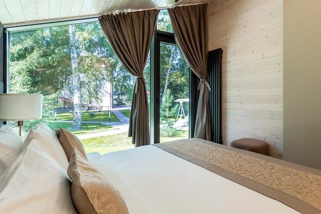 나무 침실에 흰색 침대, 이불, 베개가 있습니다. 호텔 침실. 세련된 객실에 부드러운 담요가 있는 편안한 침대