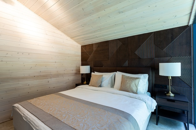 White bed,  quilt and pillows in  wooden bedroom.  hotel bedroom.  comfortable bed with soft blanket in stylish room