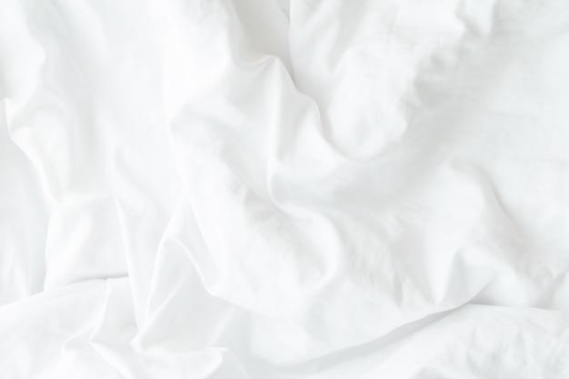 Белые постельные принадлежности или белая ткань текстура морщины, мягкий фокус