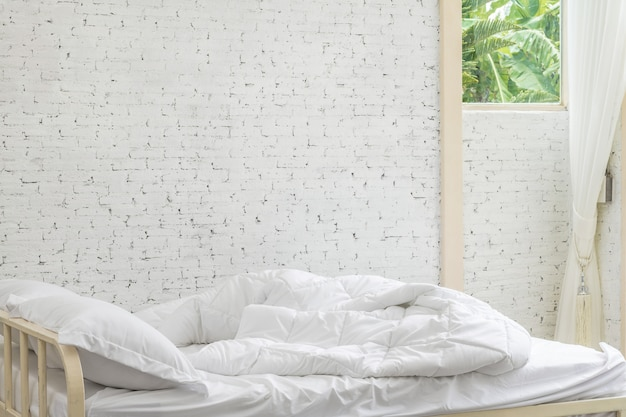 White bedding sheets and pillow in white room background.