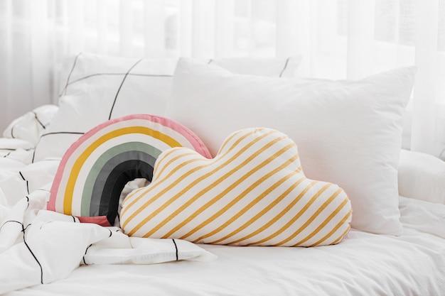 縞模様の毛布と明るい枕が付いている白い寝具シーツ。散らかったベッド。