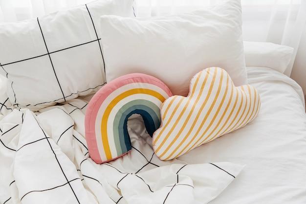 Белые простыни с полосатым одеялом и яркой подушкой. грязная кровать.