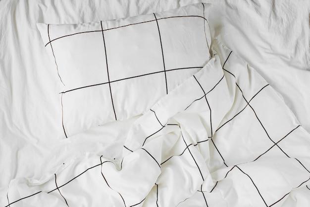 縞模様の毛布と枕が付いている白い寝具シーツ。散らかったベッド。居心地の良い背景。