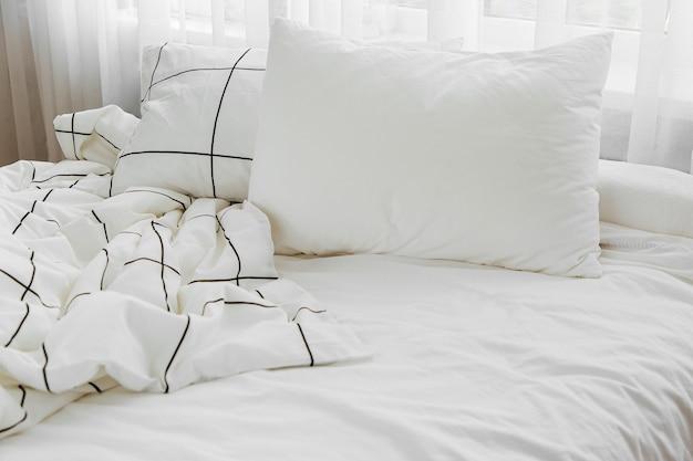 縞模様の毛布と枕が付いている白い寝具シーツ。散らかったベッド。