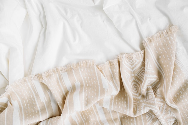 White bedding with warm plaid. cozy background with copy space. scandinavian style.