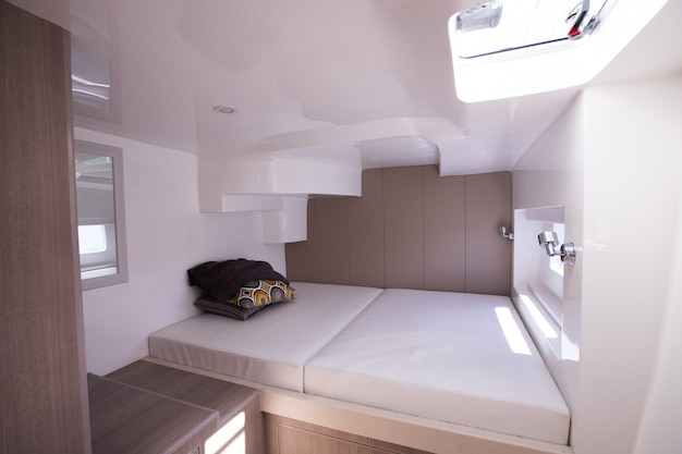 White bedroom inside yacht cruise with windows