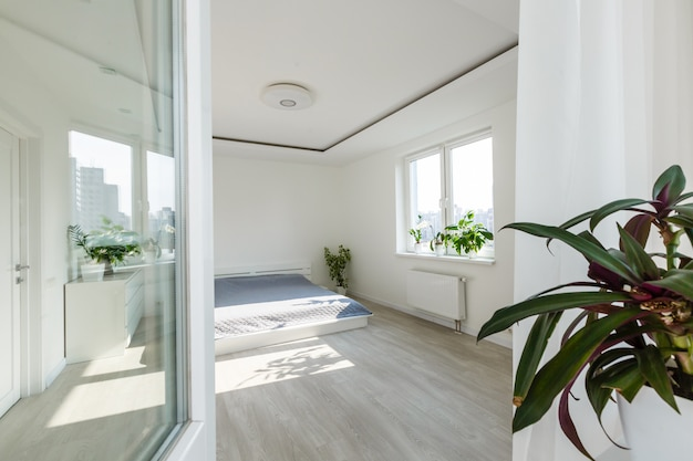 White bedroom with brick elements, balcony, double bed, desk