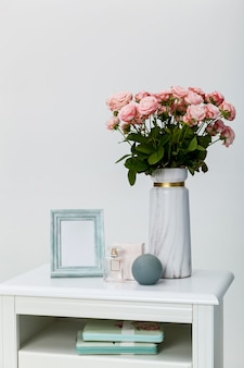 White bedside table near the bed against a white wall. on the bedside table, there are items of a vase with roses, a round candle, a photo frame, and eau de toilette