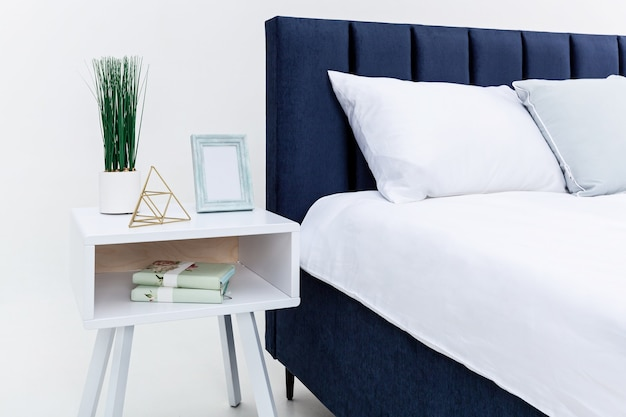 White bedside table near the bed, against a white wall. there are objects, a vase with green grass, books, a golden pyramid and a photo frame on the bedside table