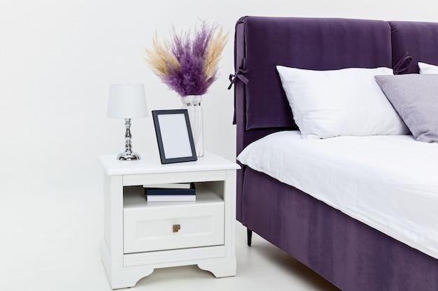흰색 벽에 침대 근처에 있는 흰색 침대 옆 탁자. 침대 옆 탁자에는 오브제, 화려한 장식의 꽃병, 책, 테이블 램프 및 사진 프레임이 있습니다.