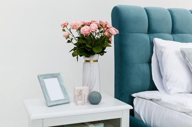 흰색 벽에 침대 옆에 있는 흰색 침대 옆 탁자. 침대 옆 탁자에는 장미꽃병, 둥근 양초, 액자, 오 드 뚜왈렛 아이템이 있습니다.