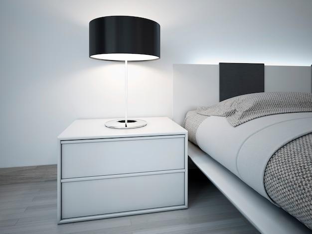 Белая тумбочка с черной лампой абажура возле кровати в современной спальне.