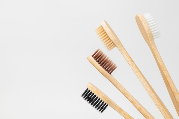 白、ベージュ、茶色、黒の竹製歯ブラシ。ゼロウェイスト、環境にやさしい。ファミリーセット。