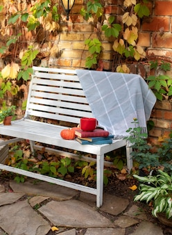 White bench in autumn garden. backyard garden grow decorative green plants and chrysanthemums. pile of books, cup of tea, plaid and pumpkin lie on wooden bench
