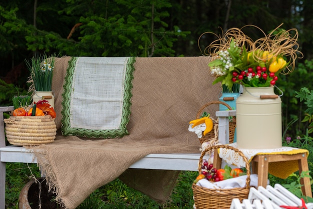 A white bench with wicker baskets of artificial flowers and fruits in the garden yard decoration