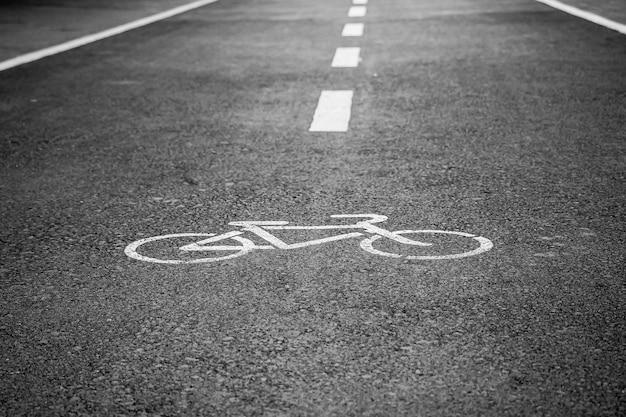 Белый знак велосипедной дорожки на поверхности асфальта