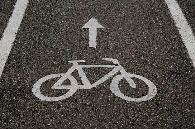 Белый знак «велосипедная дорожка» нарисован на асфальте. управление движением.