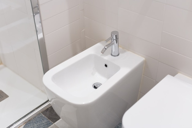 White bidet screwed to a beige tiled wall in the bathroom, close-up. white bidet with chrome mixer on the tiled floor