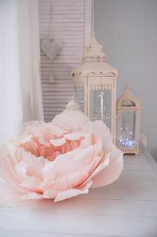 白い大きなランタンとピンクのバラの紙の花。手作りのアート装飾。結婚式の装飾